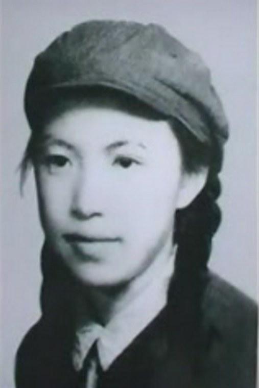 Cette image est une photographie en noir et blanc de Lin Zhao. Elle porte un habit sombre avec un col blanc, ses cheveux sont coiffés en tresses. Elle porte une casquette.