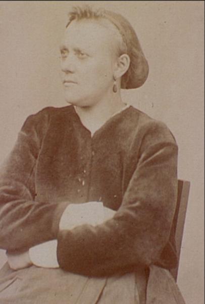 Cette image est un portrait photographie d'Eulalie Papavoine, réalisé par Eugène Appart à la prison des chantiers de Versailles. Vêtue d'une robe épaisse, elle a les bras croisés, les cheveux en chignon, et regarde vers la gauche.