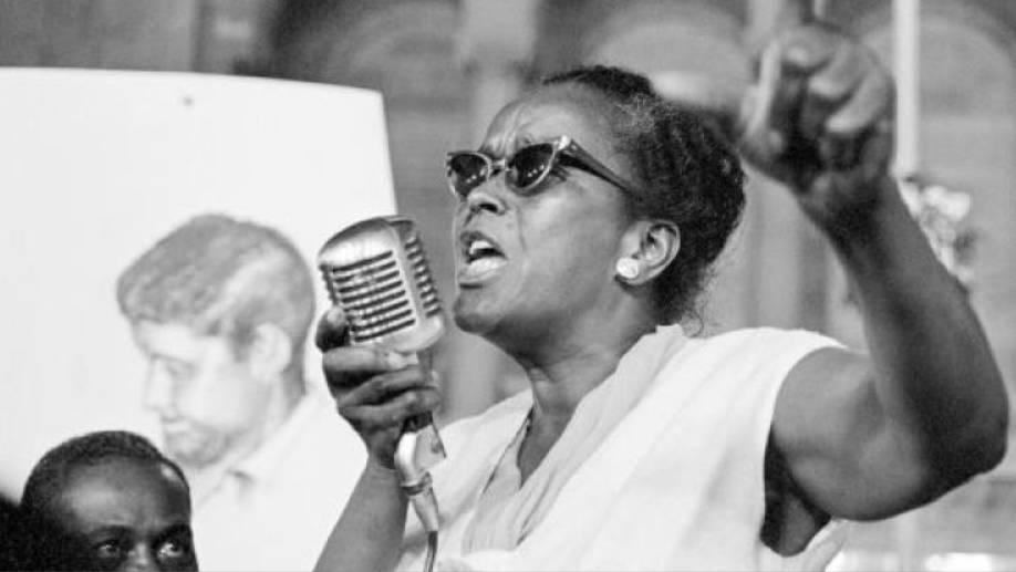 Cette photographie en noir et blanc montre Ella Baker en train de faire un discours lors d'un événement. Elle tient un micro dans sa main gauche et lève sa main droite en l'air. Elle porte des lunettes de soleil. En bas à gauche de l'image, on voit le haut du visage d'un homme afro-américain qui la regarde.