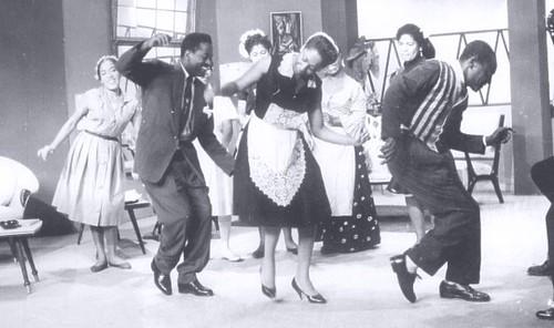 Cette photographie en noir et blanc montre Victoria Santa Cruz en train de se produire sur scène avec sa troupe de théâtre et de danse. Il y a cinq femmes et deux hommes en costumes sur scène, en train de danser.