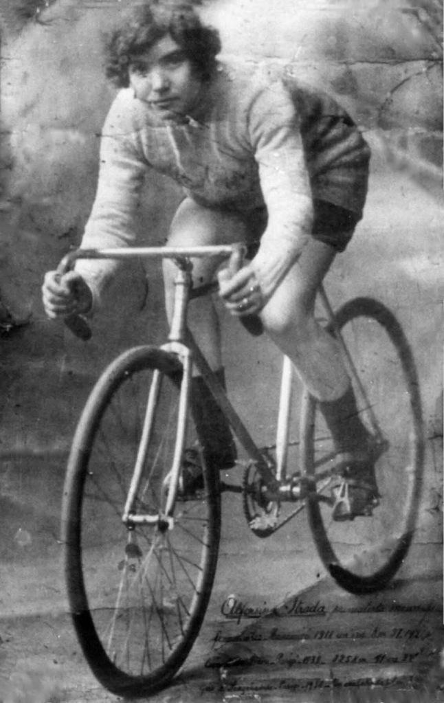 Cette photographie en noir et blanc montre Alfonsina Strada à vélo.
