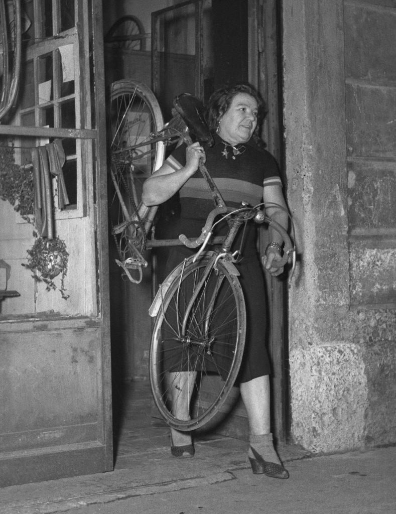 Cette photographie en noir et blanc montre Alfonsina Strada sortant de son magasin de cycles en portant un vélo par le cadre et le guidon, calé sur son épaule gauche.