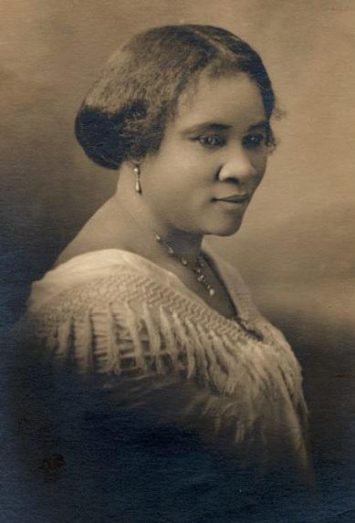 Cette photographie en noir et blanc est un portrait de Madam CJ Walker, pris entre 1905 et 1914. Elle est de profil, tournée vers la droite. Ses cheveux sont soigneusement retenus en arrière. Elle porte un vêtement blanc, un collier et des boucles d'oreille, et sourit à demi.