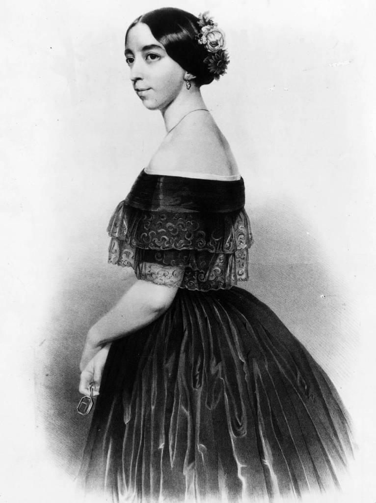 Cette image montre Pauline Viardot debout, vêtue d'une élégante robe noire dégageant ses épaules. Elle est jeune. Ses cheveux sont retenus en chignon, décoré de trois fleurs. Elle porte des boucles d'oreille. Tournée vers la gauche, elle sourit à demi.