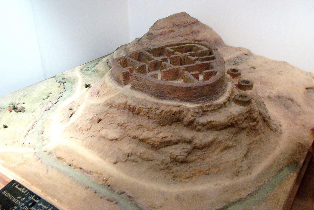 Cette photographie montre une maquette du tombeau attribué à la reine Tin Hinan. C'est un monument à chambres multiples situé au sommet d'une colline.